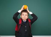 Μαθητής με το πορτοκάλι και ο σχολικός πίνακας Στοκ φωτογραφία με δικαίωμα ελεύθερης χρήσης