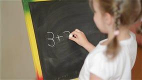 Μαθητής που ασκεί το απλό math στον πίνακα κιμωλίας απόθεμα βίντεο