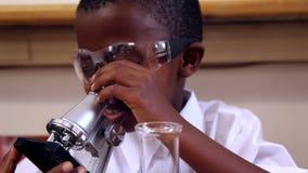 Μαθητής που κοιτάζει μέσω του μικροσκοπίου φιλμ μικρού μήκους