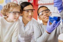 Μαθητής που παρουσιάζει φιάλη με την ουσία υπερήφανα στο δάσκαλο και στο συμμαθητή στοκ εικόνα