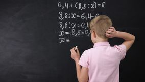 Μαθητής που προσπαθεί να λύσει math την άσκηση κοντά στον πίνακα, βασική εκπαίδευση φιλμ μικρού μήκους