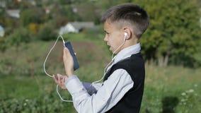 Μαθητής που στέκεται υπαίθρια και που μιλά σε μια τηλεοπτική συνομιλία μέσω του κινητού τηλεφώνου απόθεμα βίντεο