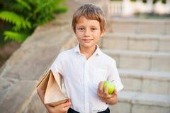 Μαθητής που χαμογελά και που κρατά μια τσάντα με το πρόγευμα και ένα πράσινο μήλο στοκ φωτογραφία