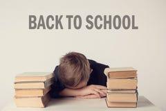 Μαθητής στο κοστούμι στο γραφείο του στο γκρίζο υπόβαθρο με τα βιβλία Το αγόρι έπεσε κοιμισμένο κατά τη διάρκεια της εργασίας επι Στοκ Φωτογραφία