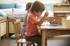 Μαθητής Montessori που εργάζεται στο γραφείο με τις ξύλινες μορφές στοκ εικόνες