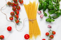 Μακαρόνια ζυμαρικών με τις ντομάτες, το σκόρδο και το βασιλικό στο άσπρο μαρμάρινο υπόβαθρο Συστατικά για το παραδοσιακό ιταλικό  Στοκ φωτογραφία με δικαίωμα ελεύθερης χρήσης
