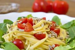 Μακαρόνια καλαμποκιού τις ντομάτες και τους σπόρους ηλίανθων που εξυπηρετούνται με με τη σαλάτα Στοκ Φωτογραφία