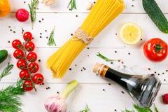 Μακαρόνια, κεράσι ντοματών, ελαιόλαδο, χορτάρι και καρυκεύματα στο παλαιό άσπρο ξύλινο υπόβαθρο Σύνολο για τα υγιή τρόφιμα Συστατ Στοκ εικόνες με δικαίωμα ελεύθερης χρήσης