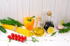 Μακαρόνια, κεράσι ντοματών, ελαιόλαδο, χορτάρι και καρυκεύματα στο παλαιό άσπρο ξύλινο υπόβαθρο Σύνολο για τα υγιή τρόφιμα Συστατ Στοκ Εικόνα