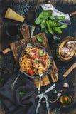 Μακαρόνια με την ντομάτα και το βασιλικό και συστατικά για την παραγωγή των ζυμαρικών Στοκ φωτογραφία με δικαίωμα ελεύθερης χρήσης