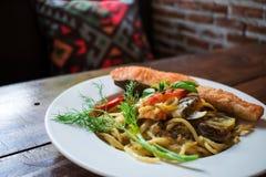 Μακαρόνια με το πράσινο κάρρυ και ένα μεγάλο κομμάτι του σολομού Σε ένα εστιατόριο στην Ταϊλάνδη Ταϊλανδικά τρόφιμα στοκ εικόνες