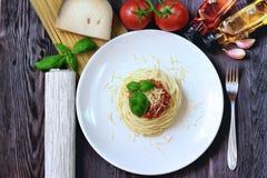 Μακαρόνια στο άσπρο πιάτο με τα ζυμαρικά και τις ντομάτες Στοκ Εικόνες
