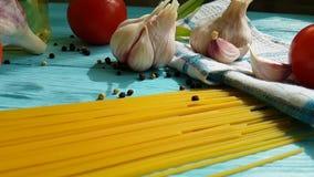 Μακαρόνια, συνταγή πετρελαίου χεριών μαγειρική ένα μπουκάλι, νόστιμο σε αργή κίνηση μαύρο πιπέρι ντοματών σκόρδου σε ένα μπλε ξύλ φιλμ μικρού μήκους