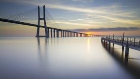 Μακριά γέφυρα πέρα από τον ποταμό tagus στη Λισσαβώνα στην ανατολή στοκ εικόνα