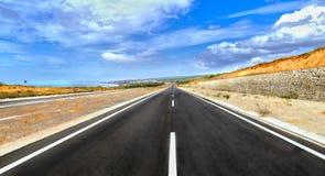 Μακριά εθνική οδός που διασχίζει την ηλιόλουστη έρημο Στοκ Φωτογραφίες