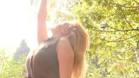 Μακριά ξανθά μαλλιά στον ήλιο Απολαύστε τη φύση το κορίτσι που χαλαρώνει στο πάρκο κίνηση αργή 4K φιλμ μικρού μήκους