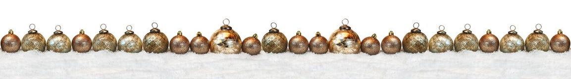 Μακριά σειρά των χρυσών σφαιρών Χριστουγέννων στο χιόνι Στοκ Εικόνα
