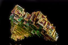 Μακροεντολή της ορυκτής πέτρας βισμουθίου σε ένα μαύρο υπόβαθρο στοκ φωτογραφία