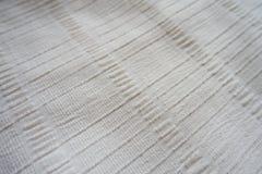 Μακροεντολή του υφάσματος κρέμας με τις αποτυπωμένες σε ανάγλυφο γραμμές Στοκ Φωτογραφία
