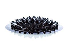 Μακροεντολή Ferrofluid στην άσπρη επιφάνεια Στοκ Φωτογραφίες
