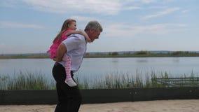 Μακροπρόθεσμος Κορίτσι με το παιχνίδι παππούδων στην παραλία Ο παππούς οδηγά μια εγγονή r φιλμ μικρού μήκους