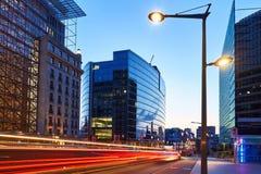 Μακροχρόνια έκθεση που πυροβολείται μιας στο κέντρο της πόλης οδού στο ηλιοβασίλεμα Ουρανοξύστες στο υπόβαθρο με τους φωτεινούς σ στοκ εικόνα με δικαίωμα ελεύθερης χρήσης