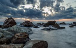 Μακροχρόνια έκθεση που πυροβολείται του ηλιοβασιλέματος στην παραλία με τους βράχους και τα σύννεφα Νότια Κέρκυρα Ελλάδα Στοκ Φωτογραφία