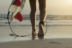 Μακροχρόνια γωνία του surfer που περπατά κατά μήκος της παραλίας με τα πτερύγια λουριών και πινάκων αστραγάλων στοκ εικόνα