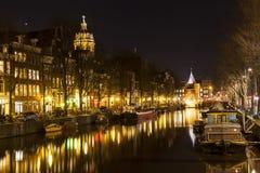 Μακροχρόνια σειρά των σπιτιών που απεικονίζει σε ένα κανάλι στο Άμστερνταμ Στοκ Εικόνα
