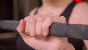 Μακρο βλαστός κινηματογραφήσεων σε πρώτο πλάνο των νέων ελκυστικών θηλυκών χεριών αθλητών που παίρνουν έτοιμων να ανυψώσει τα βάρ απόθεμα βίντεο