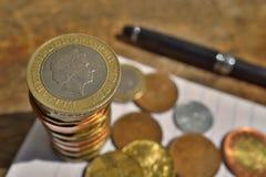 Μακρο λεπτομέρεια ενός ασημένιου και χρυσού νομίσματος σε μια αξία δύο βρετανικών λιρών αγγλίας στην κορυφή του σωρού νομισμάτων  Στοκ φωτογραφίες με δικαίωμα ελεύθερης χρήσης
