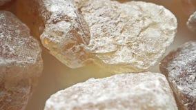Μακρο μετακινηθείτε τον πυροβολισμό των καφετιών κρυστάλλων ζάχαρης φιλμ μικρού μήκους
