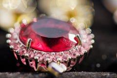 Μακρο πυροβολισμός του χρυσού κρεμαστού κοσμήματος με την πέτρα kunzite και του tourmaline στο Μαύρο, σπινθήρισμα, ηλιόλουστο υπό Στοκ Εικόνες