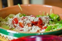 Μακρο πυροβολισμός των σπόρων ηλίανθων, σουσάμι, lin σπόροι πάνω από τις κόκκινες ντομάτες κερασιών δίπλα στο τυρί παρμεζάνας, μα Στοκ Φωτογραφίες