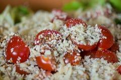 Μακρο πυροβολισμός των σπόρων ηλίανθων, σουσάμι, lin σπόροι πάνω από τις κόκκινες ντομάτες κερασιών δίπλα στο τυρί παρμεζάνας, μα Στοκ Φωτογραφία