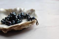 Μακρο φωτογραφία των μαύρων χαντρών μαργαριταριών με τους πολύτιμους λίθους σε ένα κοχύλι, μαρμάρινο υπόβαθρο στοκ εικόνα
