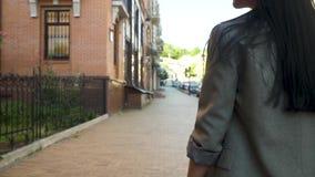 Μακρυμάλλες brunette στο γκρίζο παλτό που περπατά στην αστική οδό απόθεμα βίντεο