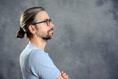 Μακρυμάλλης νεαρός άνδρας με το κουλούρι στοκ φωτογραφίες