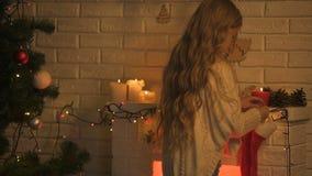 Μακρυμάλλης ξανθή κρεμώντας κάλτσα κοριτσιών στην εστία που περιμένει το θαύμα Χριστουγέννων Santa φιλμ μικρού μήκους