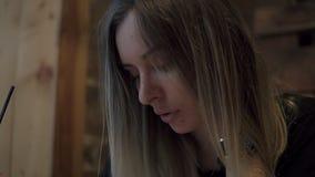 Μακρυμάλλης ξανθή συνεδρίαση γυναικών σε έναν σύγχρονο καφέ και σκεπτικά παραγωγή μερικών σημειώσεων στο σημειωματάριό της Ένα γυ απόθεμα βίντεο