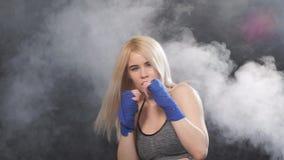Μακρυμάλλης ξανθή kickboxing κατάρτιση γυναικών στο στούντιο ικανότητας, σε αργή κίνηση φιλμ μικρού μήκους