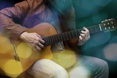 Μακρυμάλλες αρσενικό παιχνίδι κιθαριστών με την ακουστική κιθάρα στο δέρμα Στοκ Εικόνες