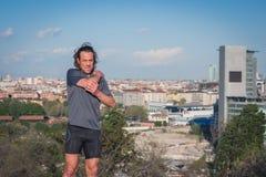 Μακρυμάλλες τέντωμα αθλητών σε ένα πάρκο πόλεων Στοκ φωτογραφία με δικαίωμα ελεύθερης χρήσης
