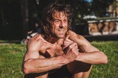 Μακρυμάλλες τέντωμα αθλητών σε ένα πάρκο πόλεων Στοκ Φωτογραφία