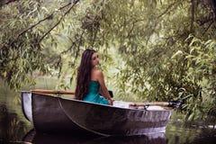 Μακρυμάλλες brunette σε μια συνεδρίαση φορεμάτων στη βάρκα Στοκ Φωτογραφία