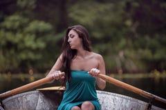 Μακρυμάλλες brunette σε μια συνεδρίαση φορεμάτων στη βάρκα Στοκ Εικόνες