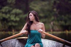 Μακρυμάλλες brunette σε μια συνεδρίαση φορεμάτων στη βάρκα Στοκ Εικόνα