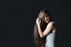 Μακρυμάλλες brunette στο μαύρο υπόβαθρο Στοκ Εικόνες