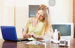 Μακρυμάλλης ανάγνωση γυναικών για τα φάρμακα σε Διαδίκτυο Στοκ Εικόνες
