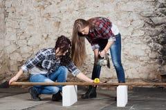 Μακρυμάλλης νέα γυναίκα δύο με έναν μύλο γωνίας Στοκ φωτογραφία με δικαίωμα ελεύθερης χρήσης